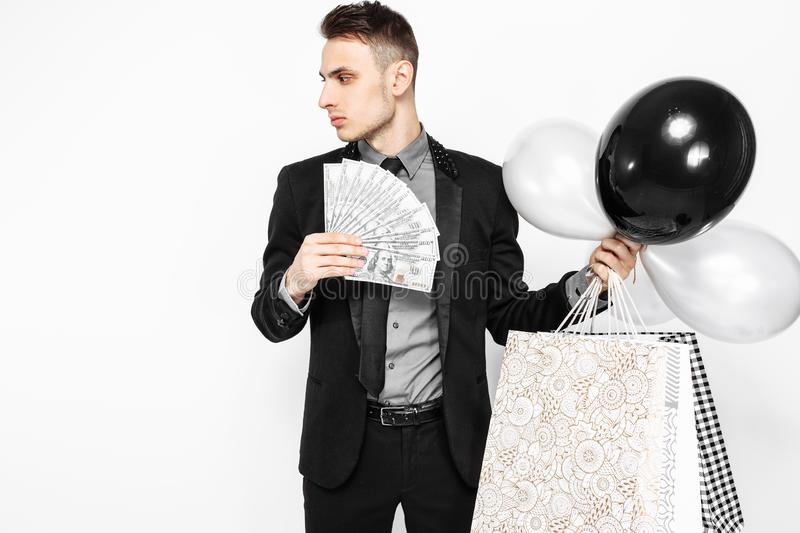 An elegant man, in a black suit, holding bags, for shopping, and. Cash, money, waiting for Black Friday. Black Friday, discounts, shopping stock image