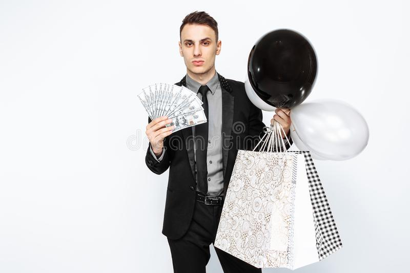 An elegant man, in a black suit, holding bags, for shopping, and. Cash, money, waiting for Black Friday. Black Friday, discounts, shopping stock photo