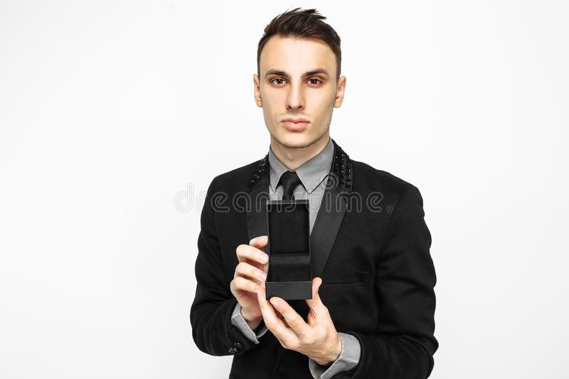 Elegant man in a black suit, holding a black case for decoration. A gift for the holiday, on a white background. black Friday, Valentine`s day gift stock photos