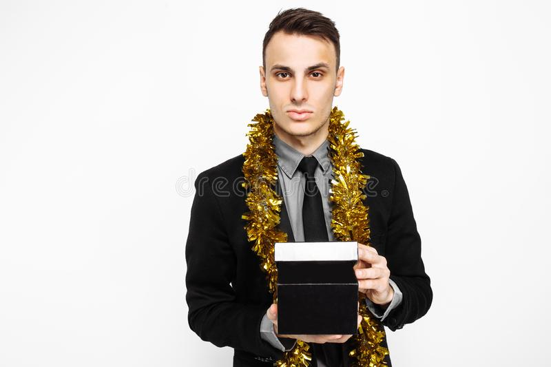 An elegant man in a black suit, and with tinsel on his neck, holding a black case, for decoration, a gift for the holiday, on a w. Hite background. black Friday stock photo