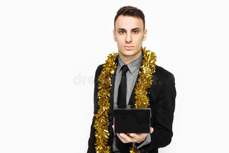 An elegant man in a black suit, and with tinsel on his neck, holding a black case, for decoration, a gift for the holiday, on a wh. Ite background. black Friday stock photography