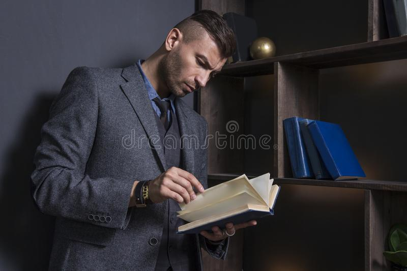 Elegant man in business suit with book. Portrait of handsome stylish man in library. Lawyer reads the book stock photography