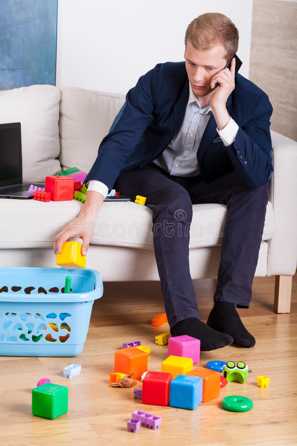 Elegant man cleaning up toys royalty free stock images