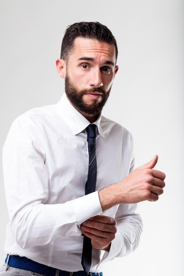 Elegant man hesitant while dressing up. Elegant man with beard hesitant while dressing up royalty free stock photo