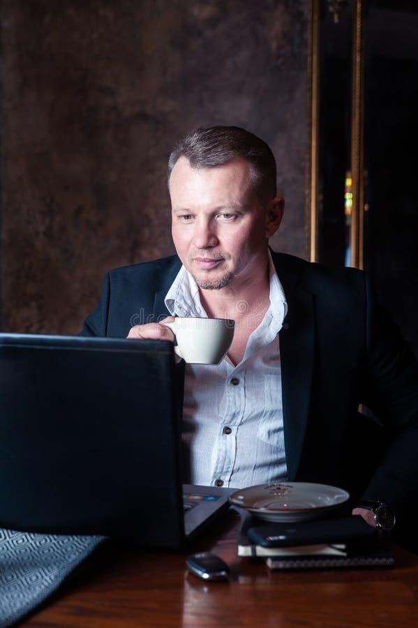 Elegant man i en chic inställning med en kopp kaffe som framme sitter av en bärbar dator arkivfoto
