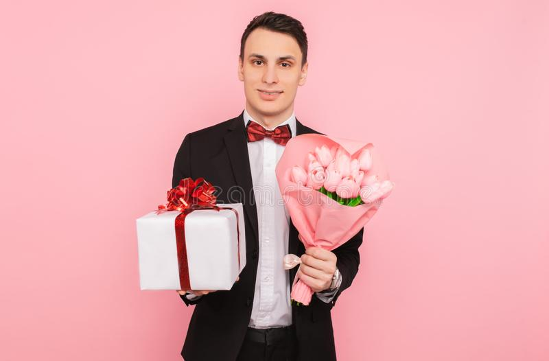 Elegant man, i en dräkt, med en bukett av blommor och en gåvaask, på en rosa bakgrund, begreppet av kvinnors dag royaltyfri foto