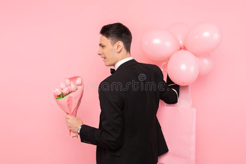 Elegant man, i en dräkt, med en grupp av blommor och ballonger, på en rosa bakgrund, begreppet av kvinnors dag royaltyfri fotografi