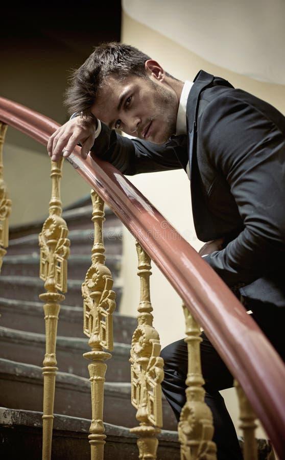 Elegant man leaing on handrail. Elegant man leaing on a wooden handrail stock photo