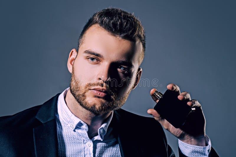 Elegant man for perfume. Masculine perfume. Fragrance. Male fragrance and perfumery, cosmetics. Man holding up bottle of. Perfumery. Cologne bottle royalty free stock image