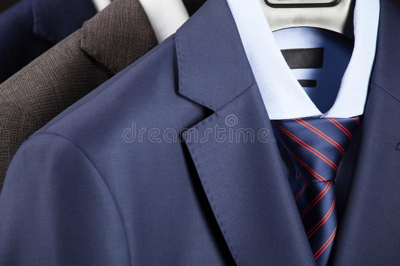 Elegant man`s suits hanging in a row royalty free stock image