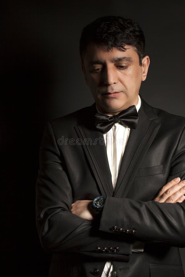 Elegant man som bär den svarta flugan och den svarta dräkten på svart backgr royaltyfri foto