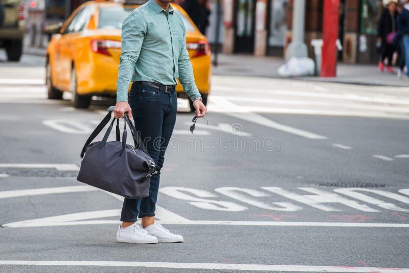 Elegant man som går på stadsgataövergångsstället som bär tillfällig kläder med jeansmyrat-shite och innehavlopppåse och solglasög royaltyfri foto