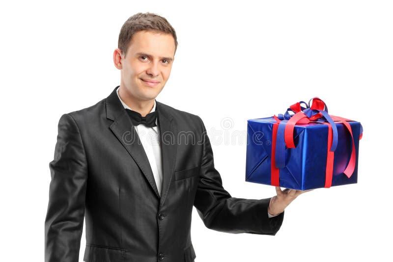 Elegant man som rymmer en gåva royaltyfri foto