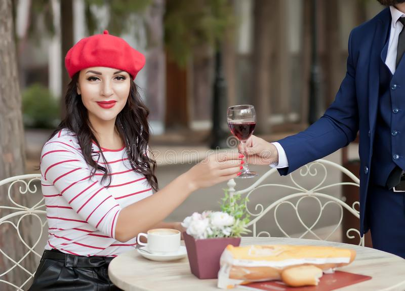 Elegant man in a suit gives a pretty brunette woman in a red cap and striped t-shirt glass of red wine in outdoor cafe stock photos