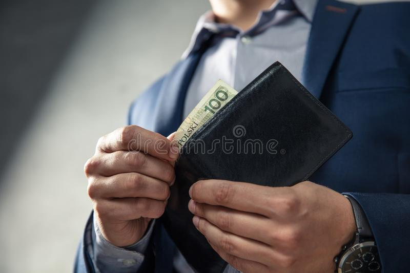 Elegant man in suit pulls out his money from wallet stock photos