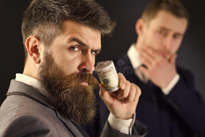 Elegant Man in Suit. Man on serious face hold roll made out of dollar, money, pay to partner. Sharing of profits concept stock photography