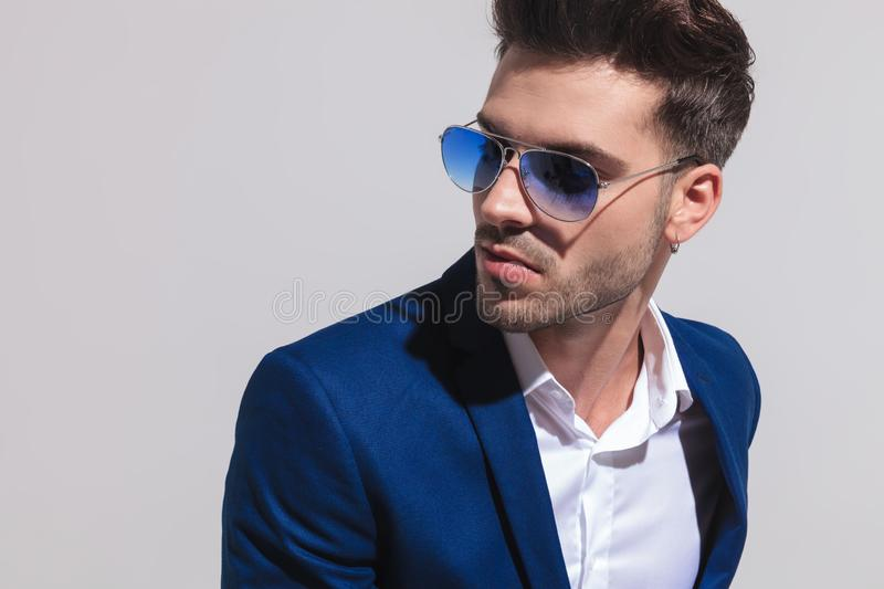 Elegant man in sunglasses looking away to side. Closeup portrait of a young elegant man in sunglasses looking away to side on grey background stock photography