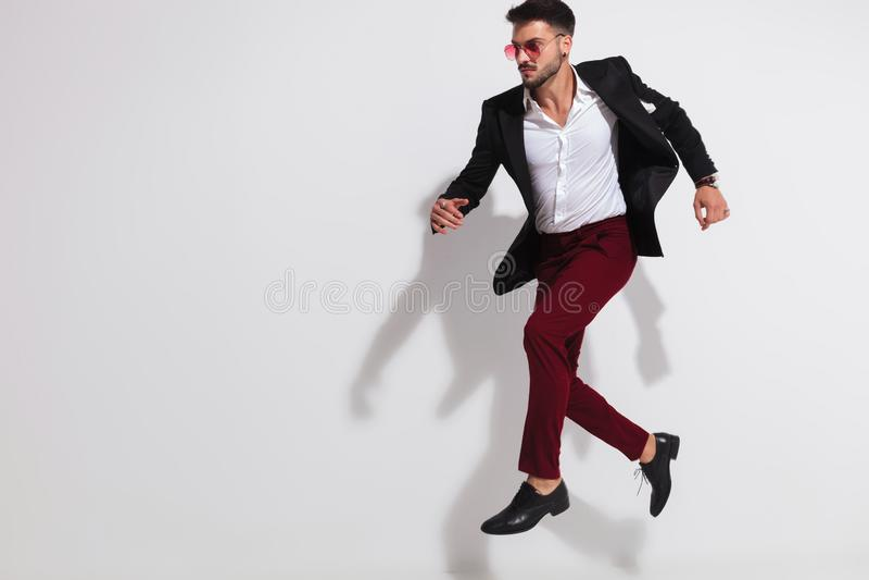Elegant man wearing black suit and sunglasses leaping to side. Elegant young man wearing black suit and red sunglasses leaping and looking to side on white stock photos