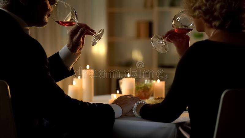 Elegant married couple drinking wine and holding hands, tender relations, spouse royalty free stock photography