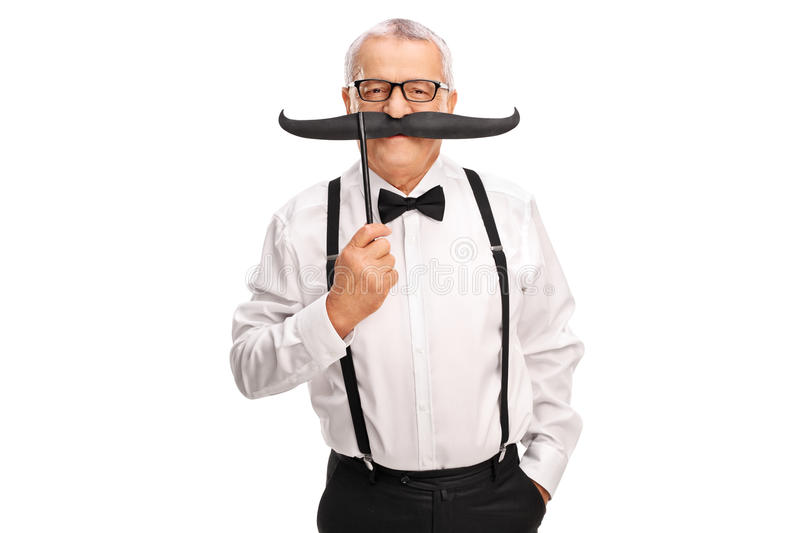 Elegant mature man holding a fake mustache royalty free stock images