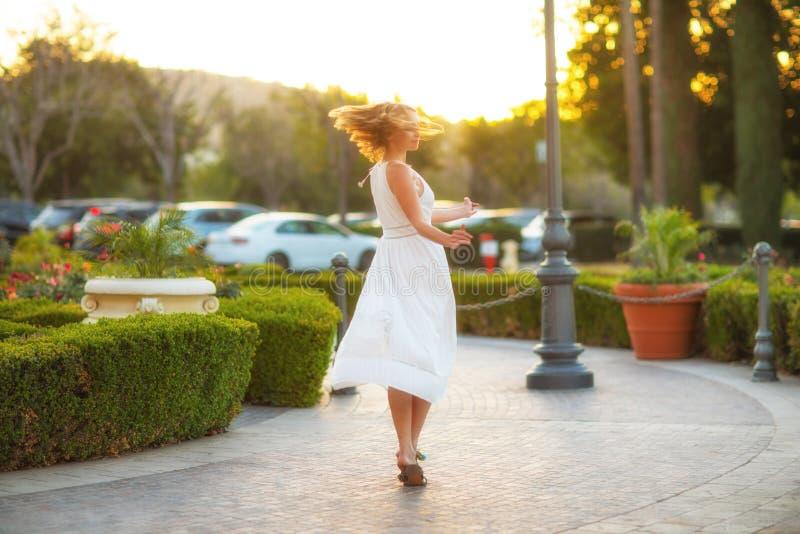 Elegant meisje in een witte kleding die zorgeloos in een straat van de zonsondergangstad dansen royalty-vrije stock afbeelding