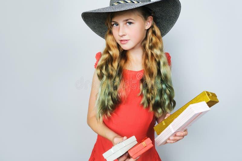 Elegant meisje met geverfte groene haaruiteinden die zich over grijze achtergrond bevinden Vakantie het winkelen en haarverzorgin stock foto