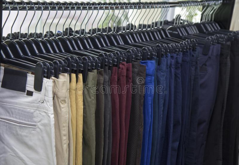 Elegant men clothing in a store, lots of  pants elegant formal wear, gentleman style , autumn spring Wedding clothes stock photography