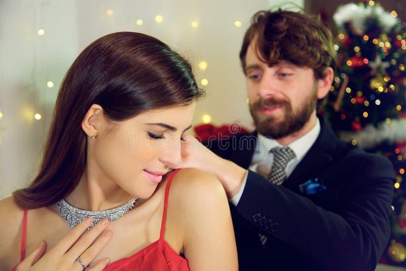 Elegant man putting necklace gift to girlfriend Christmas night smiling royalty free stock photo