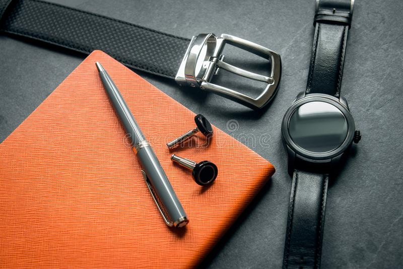 Elegant men`s business accessories. Black watches, belt, notepad, pen, cufflinks.