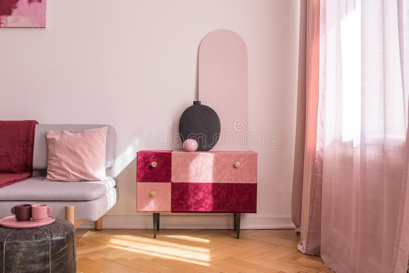 Elegant mockaskinn täckte pastellfärgat rosa, och burgundy färgade kabinettet med guld- handtag bredvid fönster i ljus vardagsrum arkivbilder