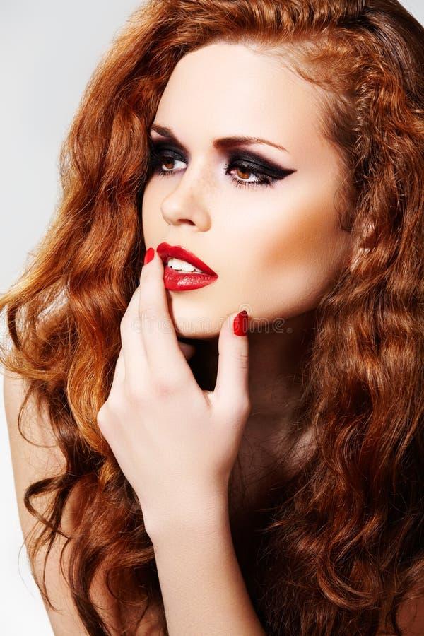 Elegant model met maniersamenstelling & lang krullend haar stock fotografie