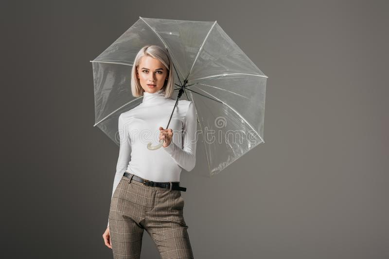 Elegant model in white turtleneck with transparent umbrella. Isolated on grey royalty free stock photography