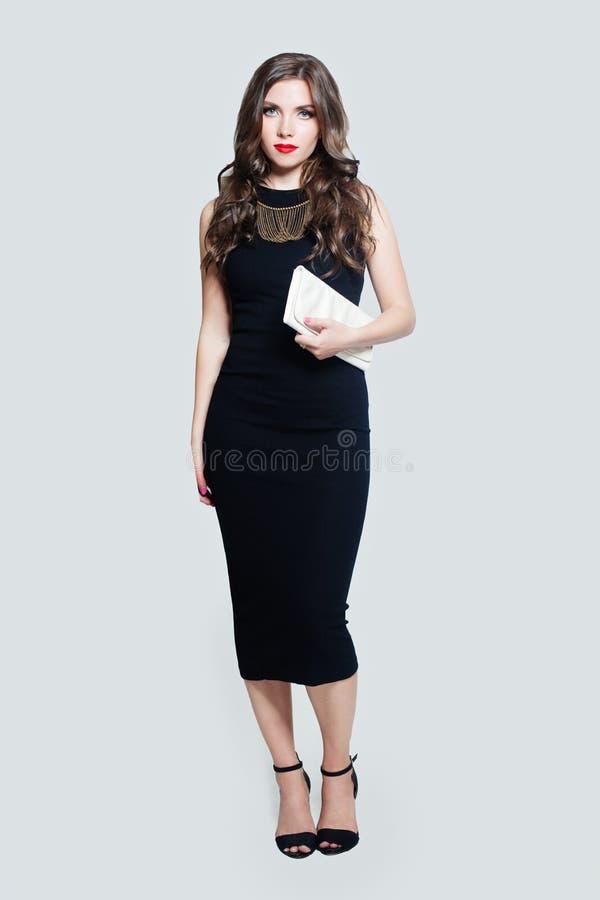Elegant model woman wearing black dress standing against white wall background stock photo