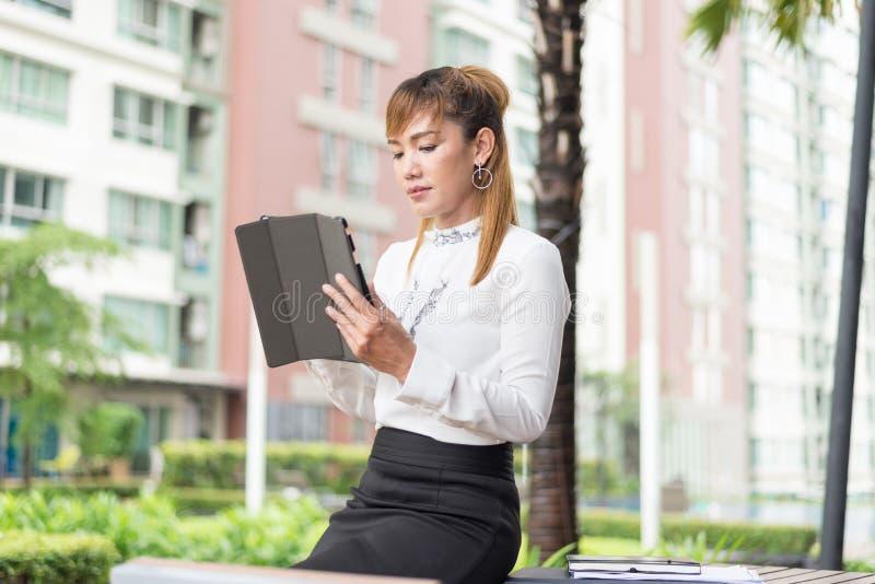Elegant modern affärskvinna som arbetar på minnestavlan arkivbild