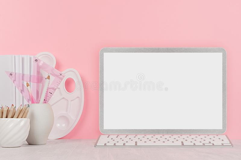 Elegant modern designers workplace with stylish silver blank computer notebook and white stationery, palette, pencils on pink/. royalty free stock images