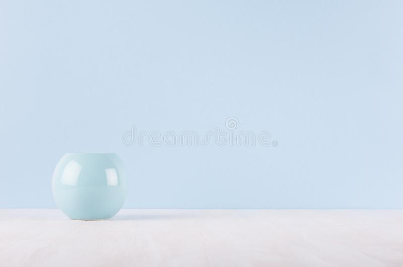 Elegant modern home decor of smooth ceramic circle vase on white wood table and light blue wall. stock photography