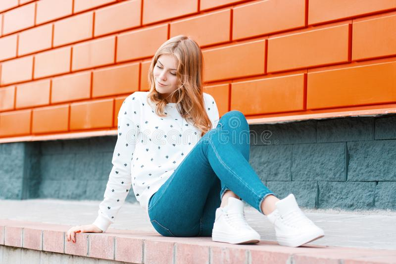 Elegant modern young cheerful woman a blonde in a white sweater in trendy jeans in sneakers sits on the ground near. The modern orange building on the street royalty free stock photography