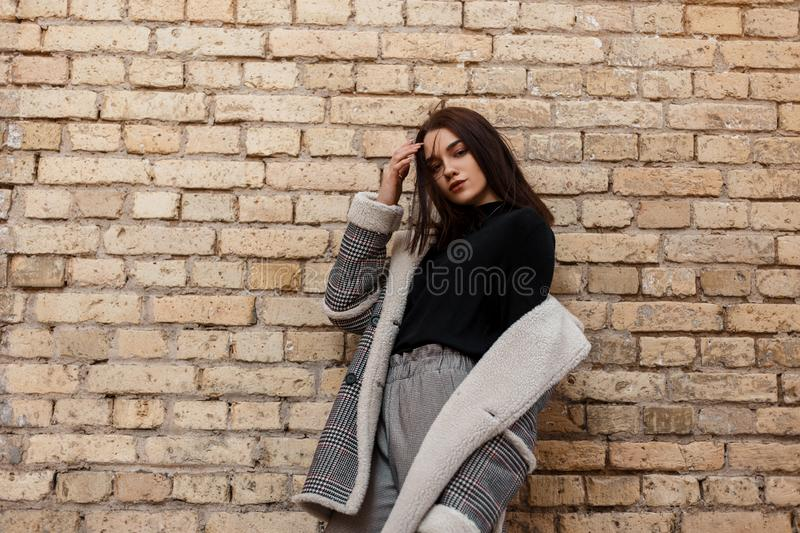 Elegant modern young woman in stylish vintage clothes in retro style posing outdoors in the city near the brick wall. In the spring day. Fashionable beautiful royalty free stock images