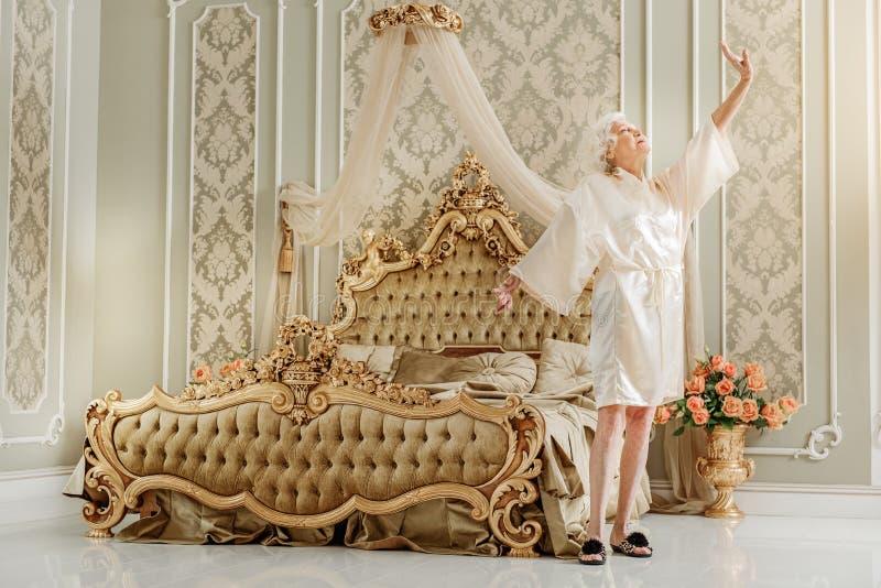 Elegant mogen dam som hemma vaknar upp royaltyfri fotografi