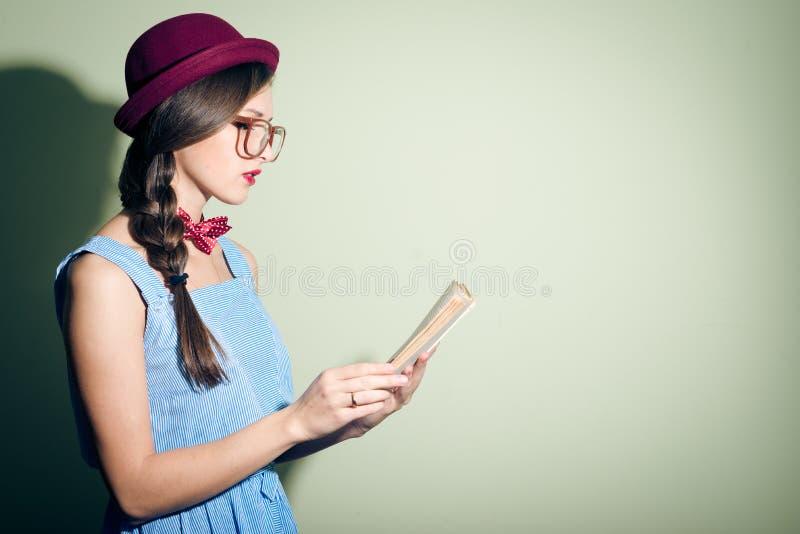 Elegant mooi meisje die in een rode hoed en glazen een boek lezen royalty-vrije stock afbeeldingen