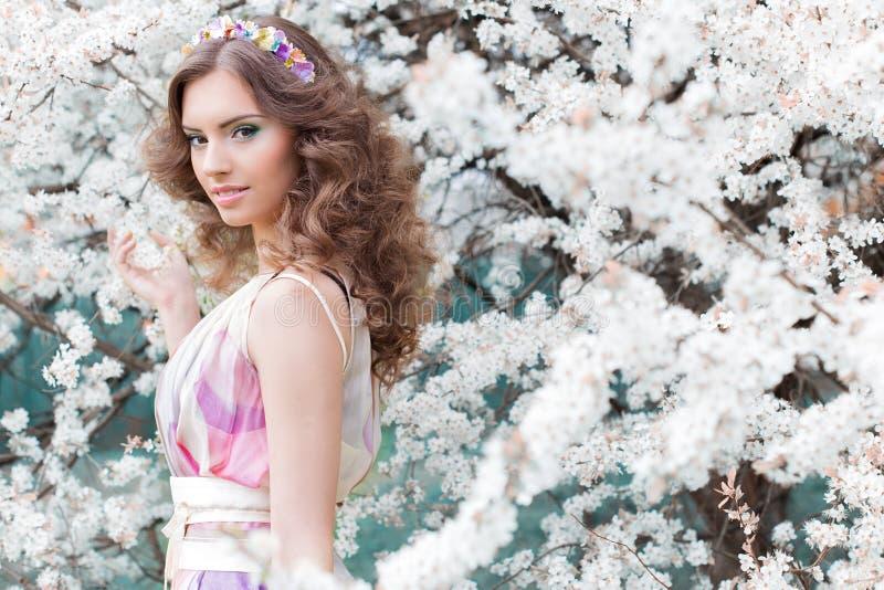 Elegant mooi meisje met weelderig haar met een rand van helder gekleurde bloemen in een tuin dichtbij een het bloeien ochtend van royalty-vrije stock afbeelding