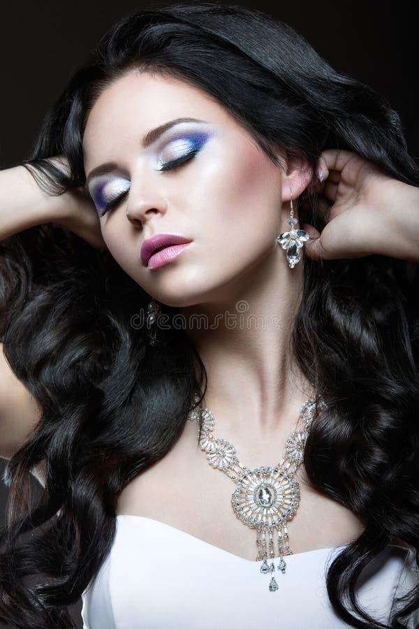 Elegant mooi meisje met zilveren make-up en zwarte krullen De winterbeeld Het Gezicht van de schoonheid stock foto's