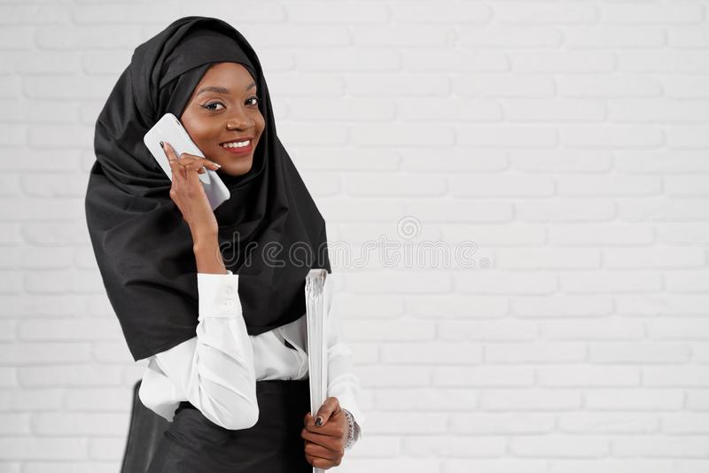 Elegant muslim woman holding phone and folder with documents stock photo