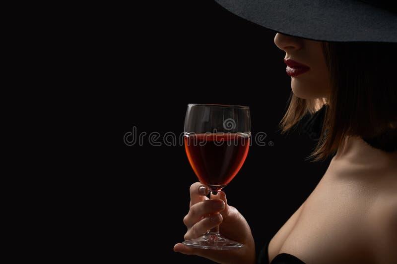 Elegant mystisk kvinna i en hatt som rymmer på ett exponeringsglas av rött vin royaltyfri fotografi