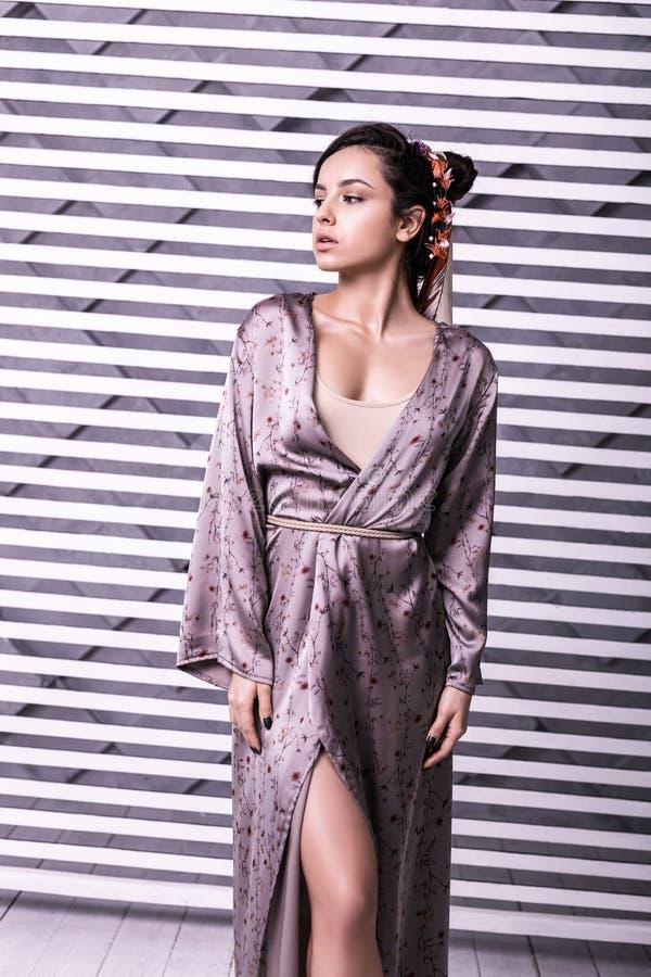 Elegant nätt supermodel som framme visar den härliga klänningen av kameran royaltyfri bild