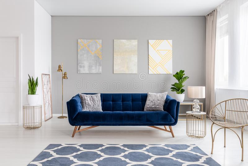 An elegant navy blue sofa in the middle of a bright living room interior with gold metal side tables and three paintings on a gray stock images