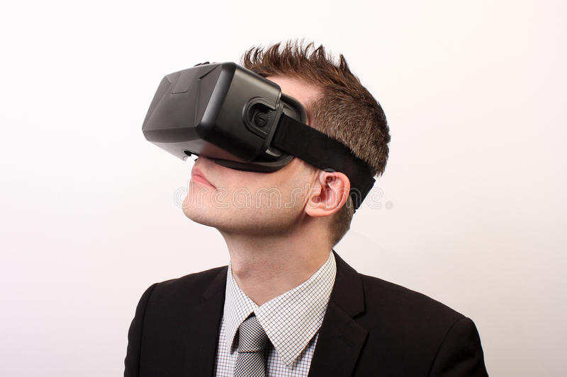Elegant, neutral man in a black formal suit, wearing a VR Virtual reality Oculus Rift 3D headset, looking upwards to the left. A man wearing Oculus Rift virtual royalty free stock image