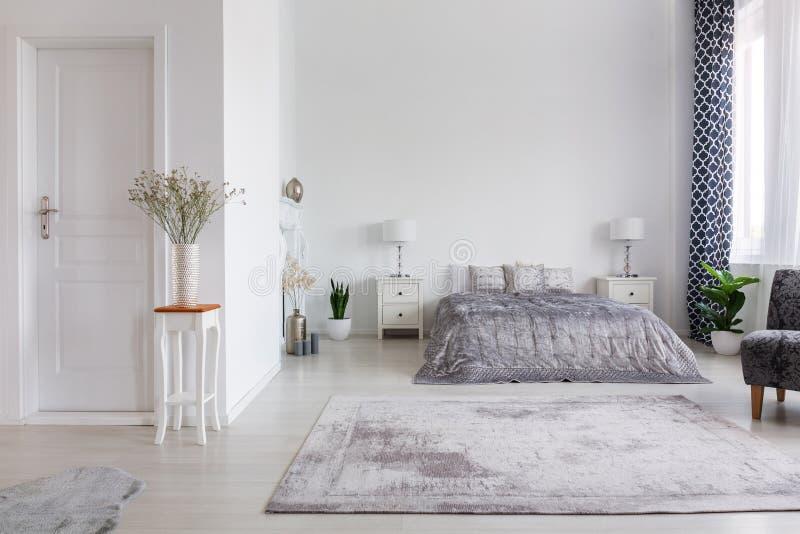 Elegant New York stilsovrum med bekväm säng, verkligt foto med kopieringsutrymme på den vita väggen royaltyfria bilder