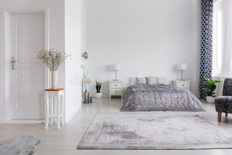 Elegant new york style bedroom with comfortable bed, real photo with copy space on the white wall royalty free stock images