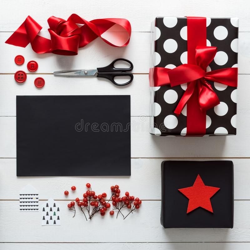 Elegant and beautiful black, red and white christmas presents, diy wrapping. Elegant nordic retro christmas, wrapping station, desk view from above, letter to royalty free stock photo